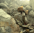 Mine worker in sulfur mine carrying heavy load Royalty Free Stock Image