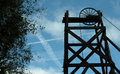 Miners wheel ancient pump and cable against softly clouded sky with tree foliage to one side Stock Image