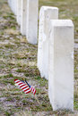 Mini american flagg faps in the wind near a grave samll marble tomb stones with small flag Stock Photography