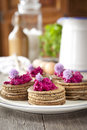 Mini buckwheat pancakes garnished with colorful beet salad and chives blossoms Royalty Free Stock Photo