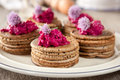 Mini buckwheat pancakes garnished with colorful beet salad and chives blossoms Stock Photo