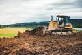 Mini bulldozer leveling ground earth for highway foundation site Royalty Free Stock Photo