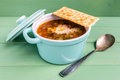 Mini casserole of minestrone soup with cracker direct view cocotte individual stays on turquoise wooden background one lies on the Royalty Free Stock Photo