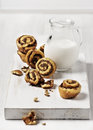 Mini cinnamon rolls and a glass of milk on a wooden cutting board Royalty Free Stock Photo