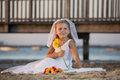 Mini flower bride a girl in a wedding dress on the beach Stock Photos
