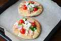 Small pizza on pita with ham, white cheese, cherry tomatoes and basil leaves Royalty Free Stock Photo