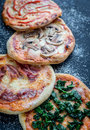 Mini pizzas with various toppings on the wooden board top view Stock Photography