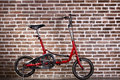 Mini red bicycle and brick wall vintage bike Royalty Free Stock Photography