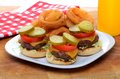Mini slider cheeseburgers with onion rings three hamburgers pickles tomatoes and cheese on a white plate Royalty Free Stock Photos