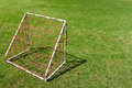 Mini small football goal for children with red net on the green Royalty Free Stock Photo