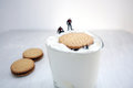 Miniature divers saving a biscuit from a yogurt glass Royalty Free Stock Photos