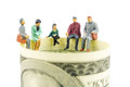 Miniature figurines discussion on the edge of 100 dollar banknote Royalty Free Stock Photo
