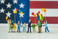 Miniature happy family holding balloons with United State nation Royalty Free Stock Photo