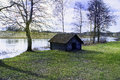 Miniature lodge a picture of a small wooden building by a river in park environment in the spring Stock Image