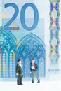 Miniature men strolling with the euro banknote background close up banknotes which feature gothic architectural style Royalty Free Stock Images