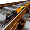 A miniature model of the train rides on big rail Stock Photos