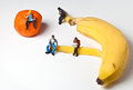 Miniature people in action stting on a banan various situations Royalty Free Stock Images