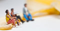 Miniature people in action stting on a banana various situations Royalty Free Stock Image