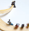 Miniature people in action stting on a banana various situations Stock Photography