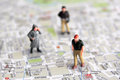 Miniature people and city map figures over Royalty Free Stock Images
