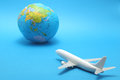 Miniature toy airplane and globe on blue background. Royalty Free Stock Photo