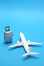 Miniature toy  airplane and suitcase on blue background. Royalty Free Stock Photo