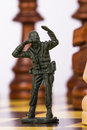 Miniature toy soldier on chess board close up view of Royalty Free Stock Photos