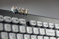 Miniature workers sitting on top of keyboard. Technology concept Royalty Free Stock Photo