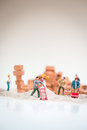 Miniature workmen doing construction work on a cloudy day with the overcast sky like background brickwork Stock Photo