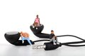 Miniatures of people enjoying music sitting on the earphones Stock Image