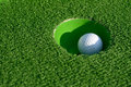 Minigolf ball in a hole Royalty Free Stock Photo