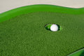 Minigolf ball in a hole Stock Photography