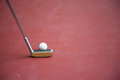 Minigolf iron racket with a white ball on a play ground Royalty Free Stock Photo