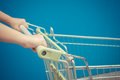 Minimalism style, Shopping cart and blue wall and human hand. Royalty Free Stock Photo