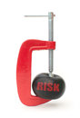 Minimizing risk clamp squeezing a ball labeled with Royalty Free Stock Photo