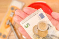 Minimum wage in europe hand holding some euro money against an out of focus mop and bucket for your or cleaning costs concepts Stock Photos