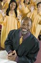 Minister at altar with bible gospel choir in background portrait Royalty Free Stock Photography