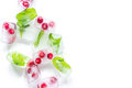 Mint and red berries in ice cubes white background top view mockup
