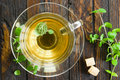 Mint tea in a transparent glass cup and fresh leaves on a wooden table Stock Photos