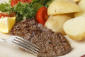 Minute steak meal closeup with fork pan grilled pepper served a salad of fresh leaves tomato cucumber and lemon boiled new Stock Photos