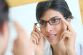 Mirror portrait of young woman trying on eyeglasses Royalty Free Stock Photo