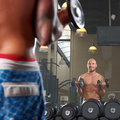 Mirror reflection of two men exercising in gym man a Stock Image