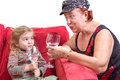 Mischievous grandmother and granddaughter trendy her beautiful little toasting each other with wineglasses of chilled water as the Stock Photo