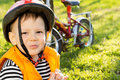 Mischievous little boy in a safety helmet impudent with cute grin and orange high visibility jacket out riding his bike the Stock Photography