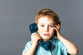 Mischievous red hair child for multi tasking communication concept young year old discussing on an old fashioned telephone and a Stock Photos