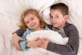 Mischievous young brother and sister in bed grinning up at the camera as they lie side by side under the duvet preparing to go to Royalty Free Stock Images