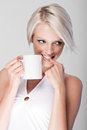 Mischievous young woman drinking coffee attractive blond with a short modern hairstyle standing and looking off to the side with a Royalty Free Stock Photo