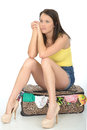 Miserable sexy bored young woman sitting on a suitcase in blue shorts and yellow vest top high heel shoes waiting to leave Royalty Free Stock Image