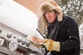 Miserable winter barbequer snow continues to fall on a middle aged man as he goes to light his barbeque only to find it covered in Royalty Free Stock Image
