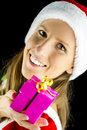 Miss santa holding a christmas present portrait of over black background Stock Photo
